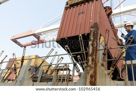 Cargo container worker - watching the loading plan .