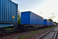 Cargo Containers Transportation On Freight Train By Railway. Intermodal Container On Train Car. Rail Freight Shipping Logistics Concept. Import - export goods from Сhina. Motion, Out of focus