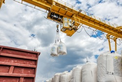 Cargo crane lifts two large bags of ammonium nitrate. Big yellow gantry crane. The work of lifting equipment in the warehouse.