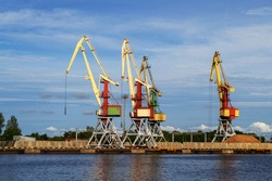 Cargo cranes in terminal in river ship port in Ventspils, Latvia, Baltic sea. Shipping import or export, logistic. Storage, port cranes, industrial scene. Venta river.