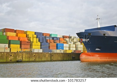 cargo freight containers stacked at harbor terminal with big container-ship