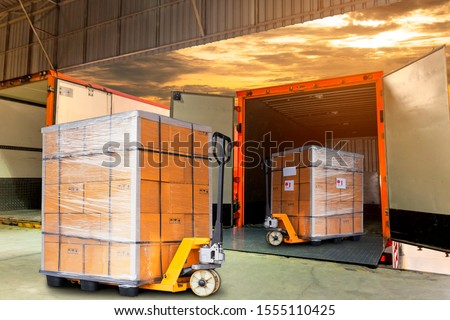 Cargo freight, Shipment, Delivery service. Logistics and transportation. Warehouse dock load pallet goods into shipping container truck. Stacked package boxes on pallet inside a truck.