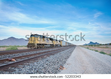 Cargo locomotive railroad engine crossing Arizona desert wilderness during early evening. - stock photo