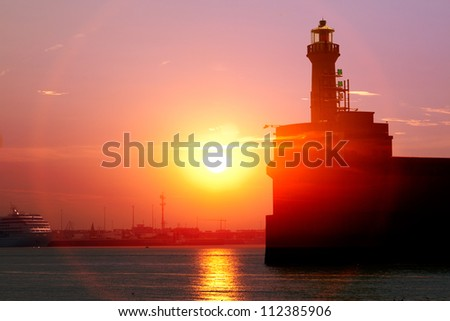Cargo sea port. Old lighthouse. Sea cargo cranes. Sunrise.