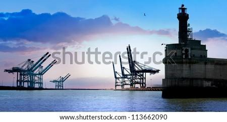 Cargo sea port. Old lighthouse. Sea cargo cranes. Sunrise. Panorama.