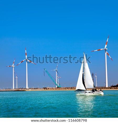 Cargo sea port. Wind turbines. Sea. Yacht.