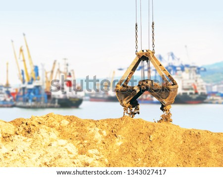 Cargo sea port, work. Unloading sand. Grapple lifting device for port cranes for bulk materials, iron scoop #1343027417