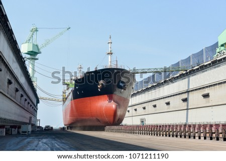 Cargo ship at floating dry dock is being renovated and Crane on dock background in shipyard Thailand