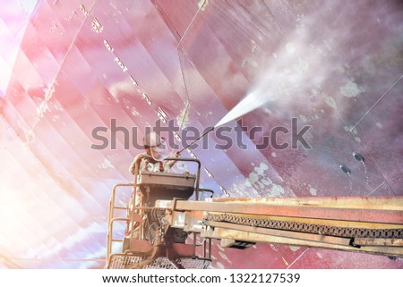 Cargo ship external wall cleaning shell are doing these people at shipyard in Thailand