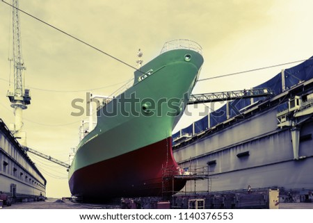 cargo ship green during repair on floating dock and crane working on dock in shipyard Thailand on vintage tone
