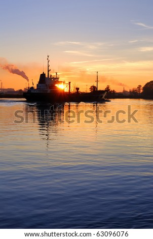 cargo ship leaving port at the sunset
