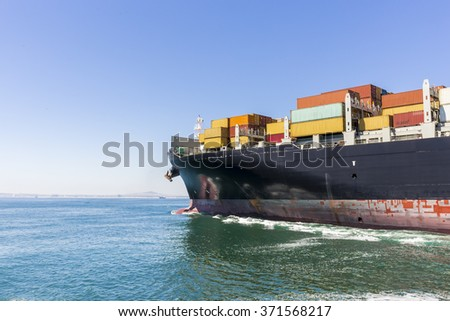 Cargo ship loaded with containers sailing away.