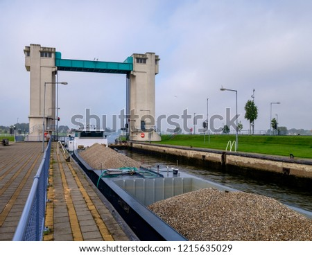 Cargo ship loaded with gravel. waiting in a lock to be lift-locked, to continue its journey Stockfoto ©