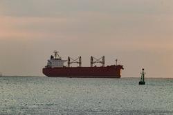 Cargo ship near signaling buoys.