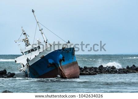 Cargo ship run aground on rocky shore #1042634026