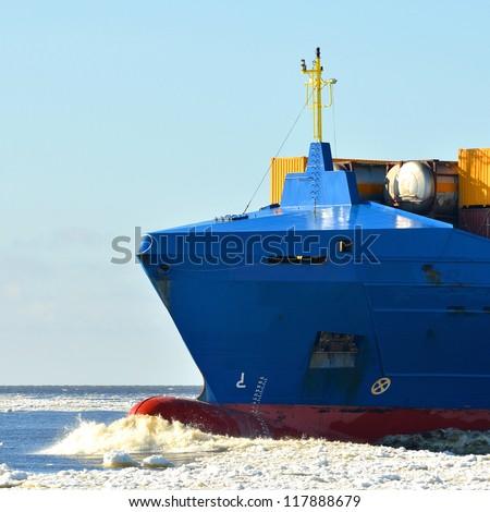 cargo ship sailing in sea full of ice in winter