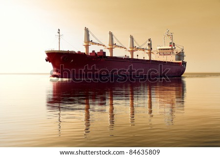 cargo ship sailing in still water against sunset sky