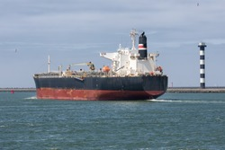 Cargo ship sailing out of Dutch harbor Rotterdam, biggest seaport of Europe