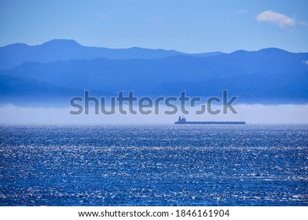 Cargo ship shimmers in sun at edge of fog bank - below Washington's Olympic Mountains - as it heads out to the open waters of the Pacific Ocean Stock fotó ©