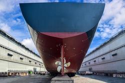 Cargo ship stern moored in floating dry dock propeller center of rudder, slipper wood, Big ship rear view under Repair, maintenance already in shipyard Thailand