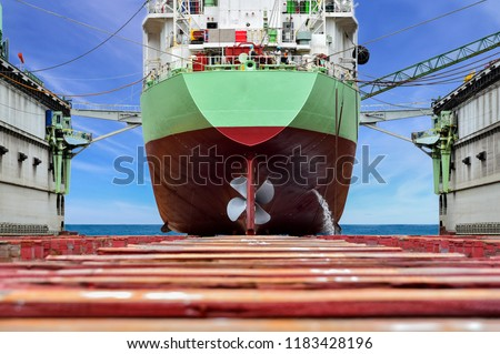 Cargo ship stern moored on sleeper ship after maintenance Large ship rear view with propeller rudder under Repair at floating dock in shipyard