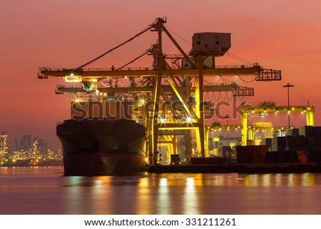 Cargo ship to light in the morning before sunrise.