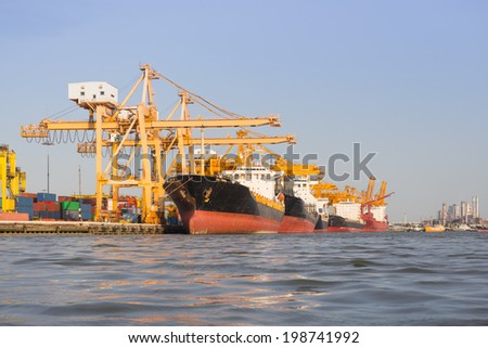 Cargo ship unloading container at port day time