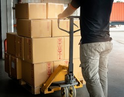 Cargo shipment boxes, Warehousing. Worker working with hand pallet truck unloading cargo boxes on pallet at the warehouse.