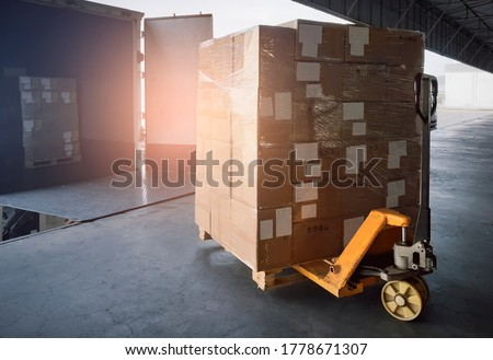 Cargo shipment loading for truck. Stacked of shipments boxes on pallet  with hand pallet truck waiting for load into a truck. Road freight cargo industry. Logistics and transportation.