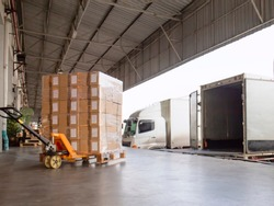 Cargo shipment loading for truck.  Warehousing logistics and transportation, hand pallet truck with cargo pallet shipment, trucks docking load cargo at warehouse.