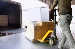 Cargo shipment loading for truck. Worker courier unloading cargo pallet shipment goods, package box, his using hand pallet  jack load into a truck, Road freight truck transportation.