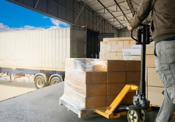 Cargo shipment loading for truck.Worker courier unloading cargo pallet shipment goods, package box, his using hand pallet jack load into a truck, Road freight transport. Industrial warehouseing.