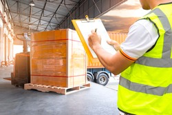 Cargo shipment loading for truck.Worker holding clipboard, his inspecting document with cargo. Forklift pallet jack with pallet goods. Freight truck, Shipping warehouse, Logistics and transport.