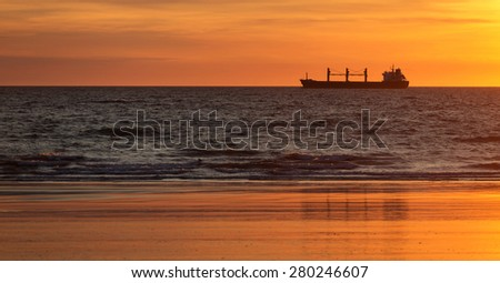 Cargo ships in the ocean at sunset