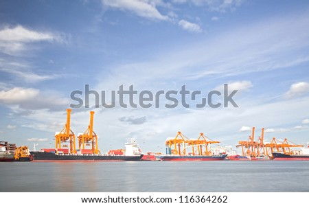 Cargo Ships Loading and unloading goods container with cranes at Port Terminal with beautiful cloudscape for heavy industry and logistic background