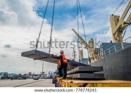 cargo steel slab discharging from the ship vessel laying onto the lorry trailer tier to tier, the shipment export and import under logistics system services to global worldwide transportation #778778245