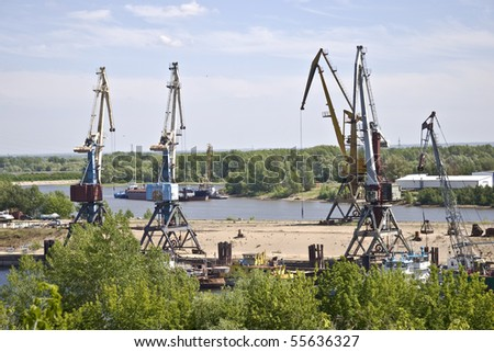 Cargo terminal for ships and barges on the river bank. Industrial landscape.