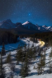Cargo train making its way through Bow Valley at Morant's Curve during a starry winter night. Banff National Park, Alberta, Canada, Canadian Rockies. Blue winter tones, cold, freezing transportation.