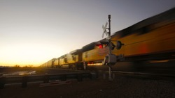 cargo train passing a railroad crossing at dawn