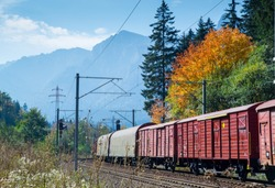 Cargo train with multiple wagons on railroad with autumn colors in the forest. Mountains and blue sky in the background.