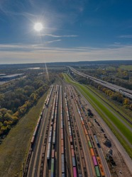 Cargo trains. Aerial view of colorful freight trains near highway. Railway station. Wagons with goods on railroad. Heavy industry. Industrial scene with trains and sun stern at the blue sky.