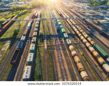 Cargo trains. Aerial view of colorful freight trains. Railway station. Wagons with goods on railroad. Heavy industry. Industrial scene with trains, railway platfform at sunset.Top view from drone