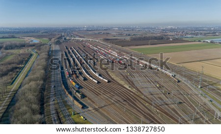 Cargo trains. Aerial view of colorful freight trains. Railway station. Wagons with goods on railroad. Heavy industry. Industrial scene with trains, city buildings and sky at sunset. Top view drone #1338727850