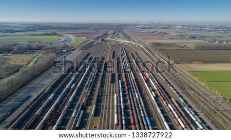 Cargo trains. Aerial view of colorful freight trains. Railway station. Wagons with goods on railroad. Heavy industry. Industrial scene with trains, city buildings and sky at sunset. Top view drone #1338727922