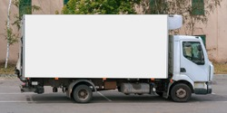 cargo truck with big empty bodywork with white mock-up place for advertising commercial information stands outside on city street business logistics concept