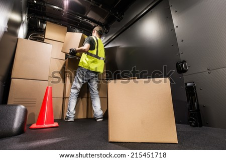 Cargo Van Loading by Worker. Man Carrying Boxes In the Cargo Van For Customer Delivery. Shipment Preparation and Processing.
