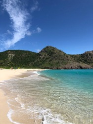 Caribbean beach and turquoise waters set against lush unspoiled hills