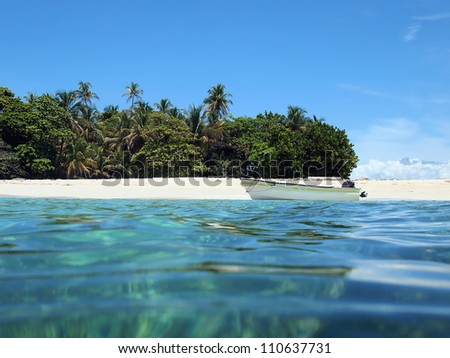 Caribbean beach on a island with tropical vegetation and a boat on the shore viewed from sea surface