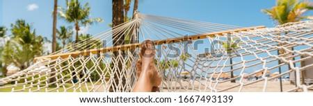 Caribbean beach selfie girl relaxing on hammock panoramic banner travel background panorama. Summer travel vacation holidays.