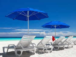 Caribbean beach with blue sun umbrellas and white sunbeds. Christmas vacation. Santa hat on sun chair